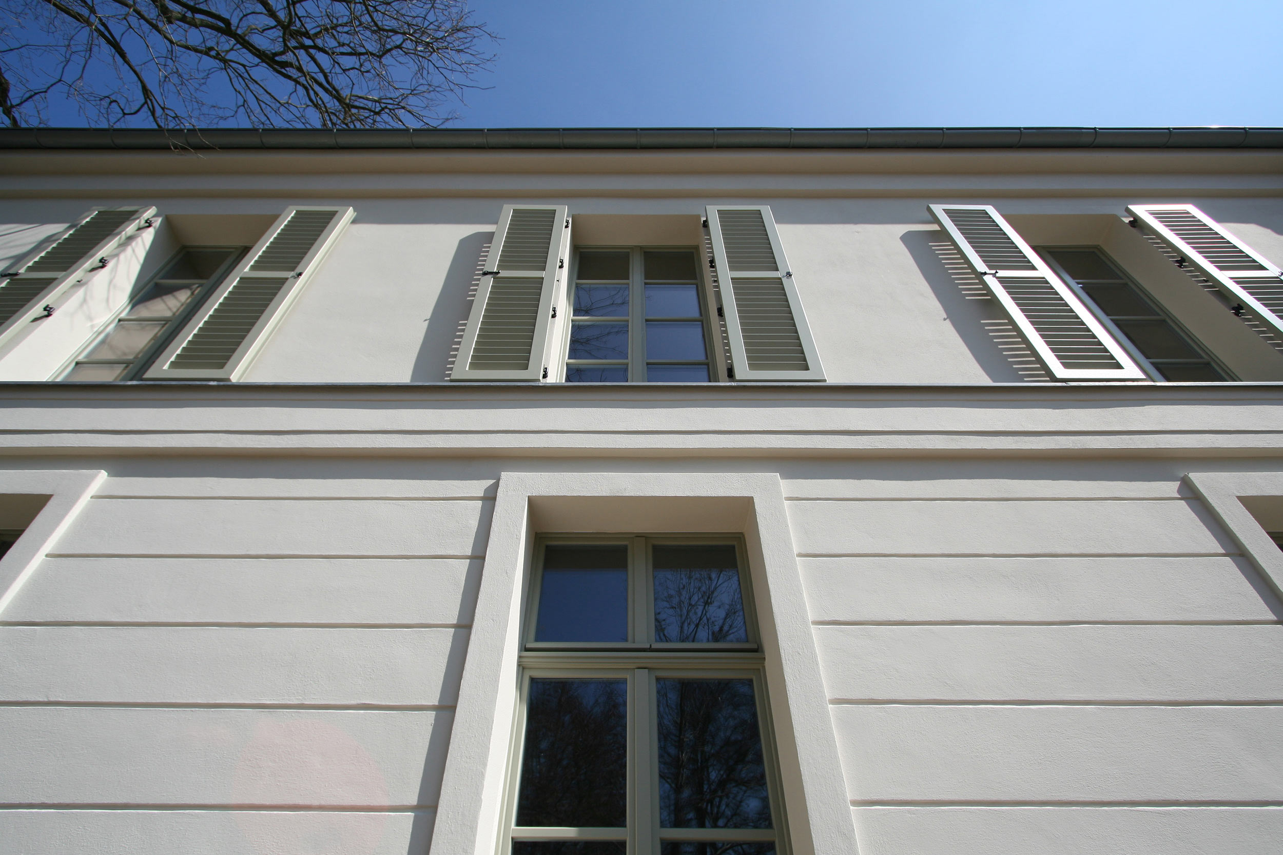 Holzfensterläden, Gesimse und Faschen erzeugen einen lebendigen Schattenwurf.