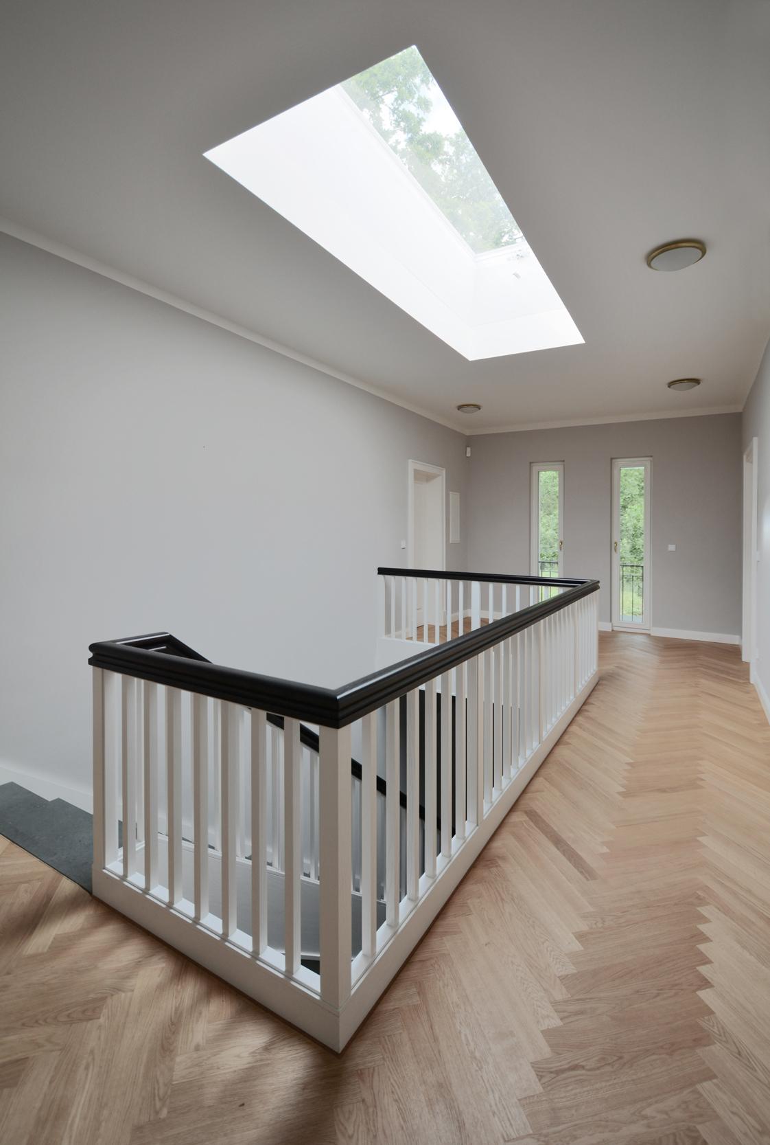 Die Galerie im Obergeschoss mit einer Balustrade in der Geometrie des Oberlichts.