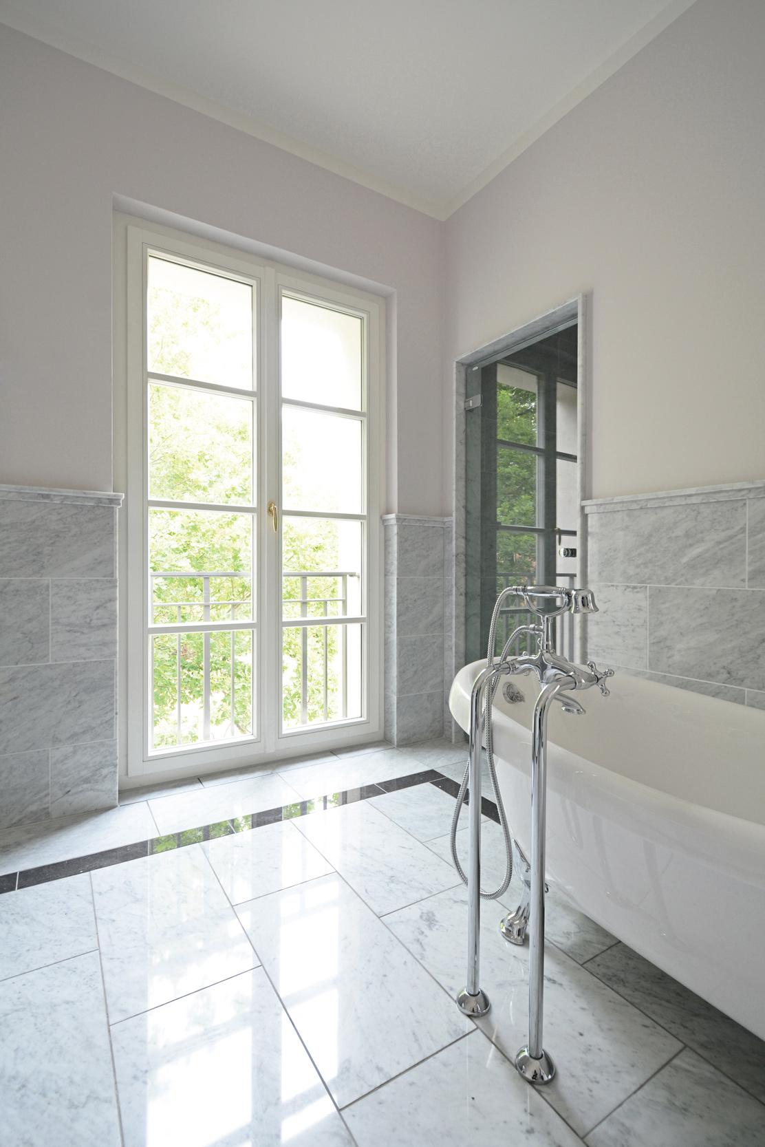 Das helle Masterbad mit Wandverkelidung und Böden aus Marmortafeln.