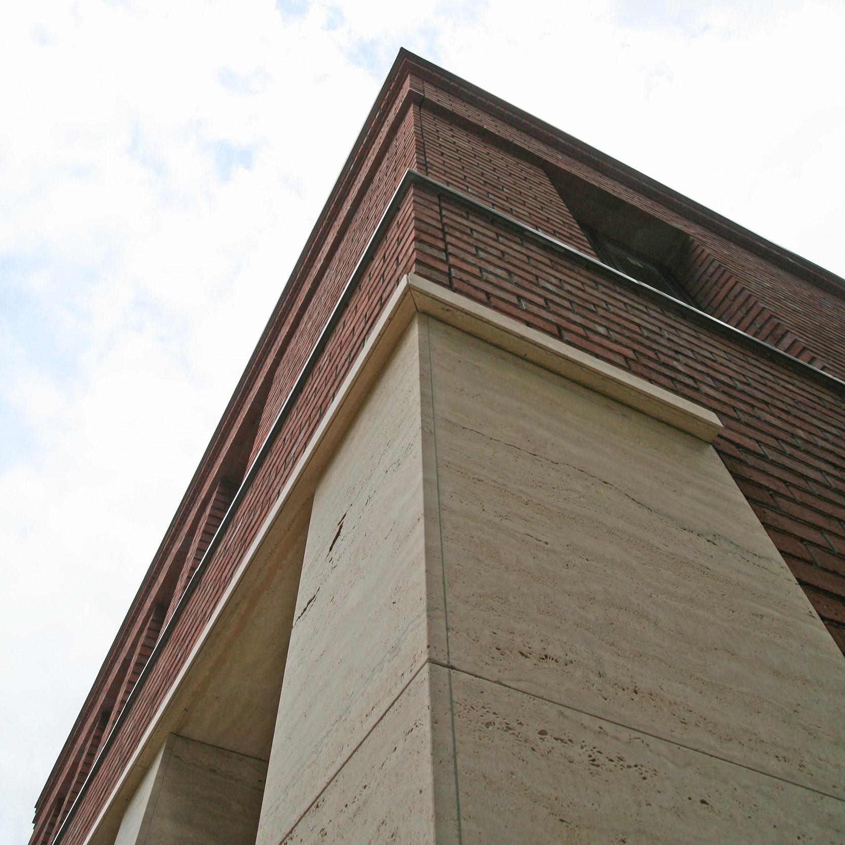 Die Klinkerfassade im Läuferverband ist mit Gesimsen aus Backstein und Travertin gegliedert