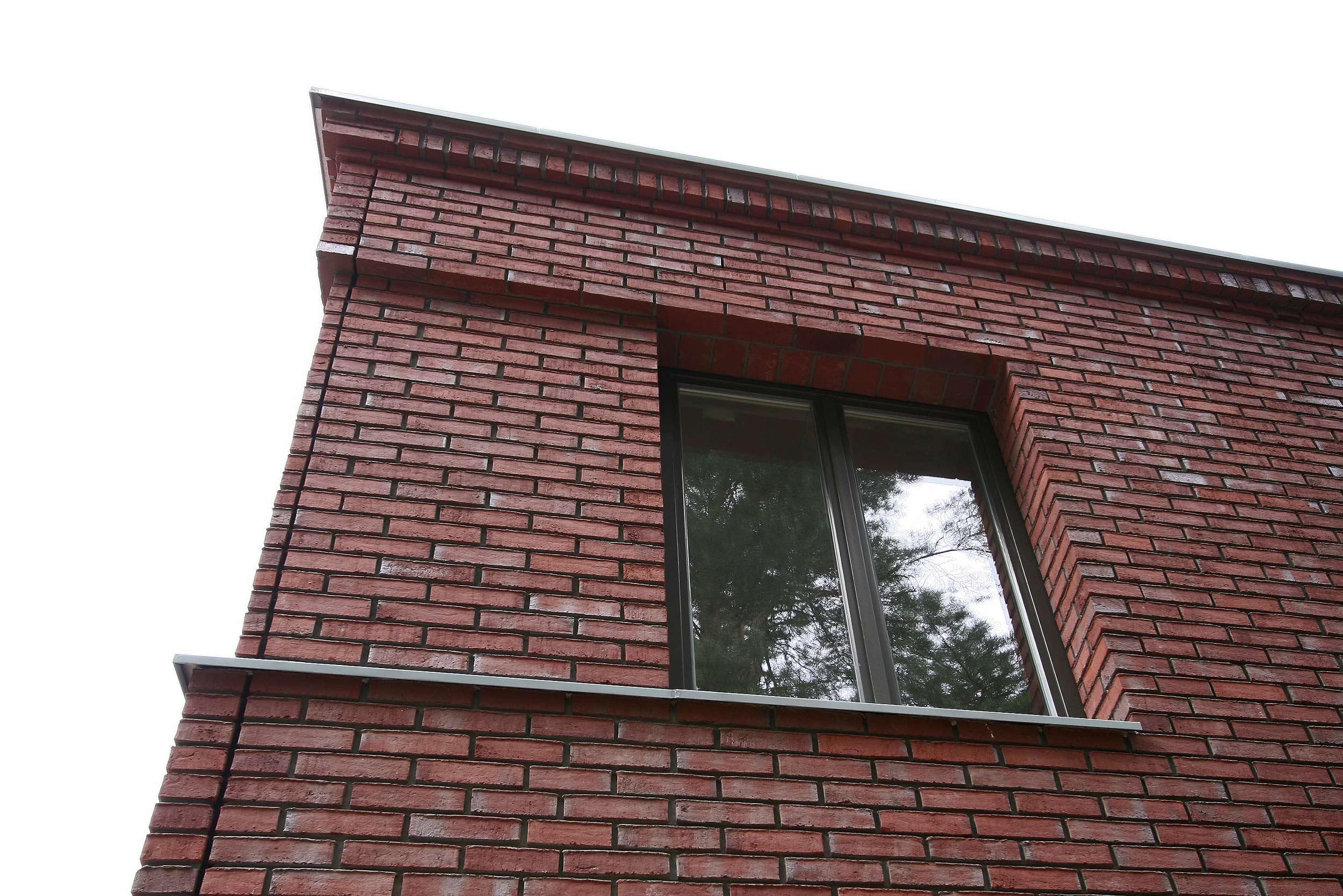 Die Fenster im Obergeschoss werden durch ein Rücksprung in der Fassade zusammengefasst