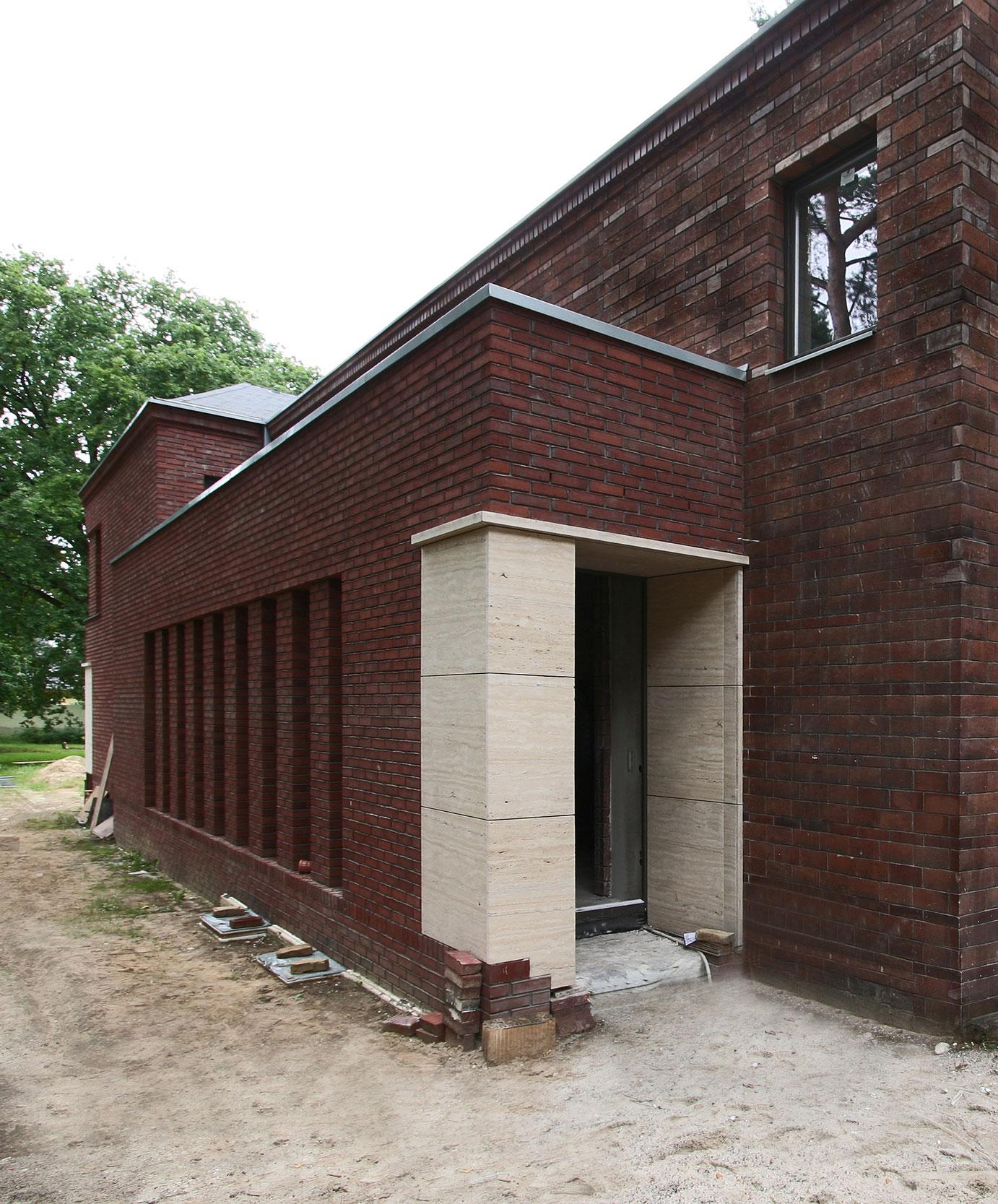 Der Eingangsbereich aus Travertin ist duch schmale Galeriefenster belichtet
