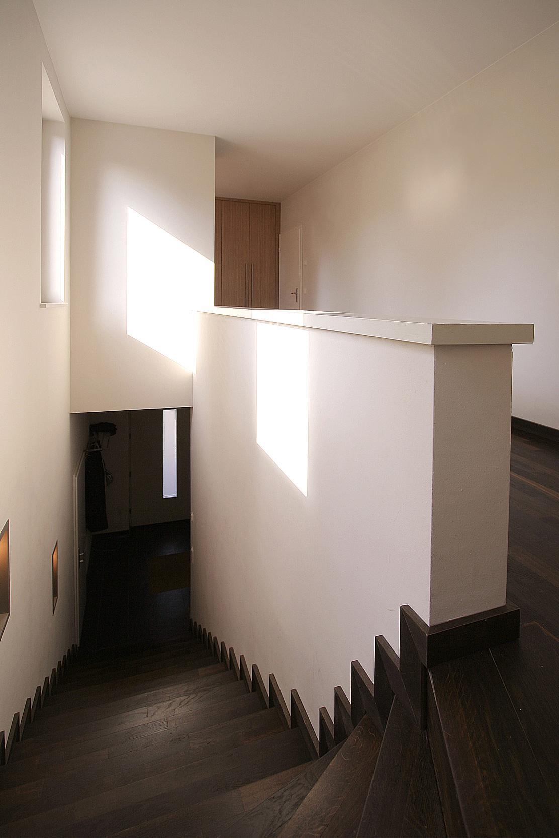 Die lichtdurchflutete Treppenhalle ist mit dunklem Holzparkett belegt.