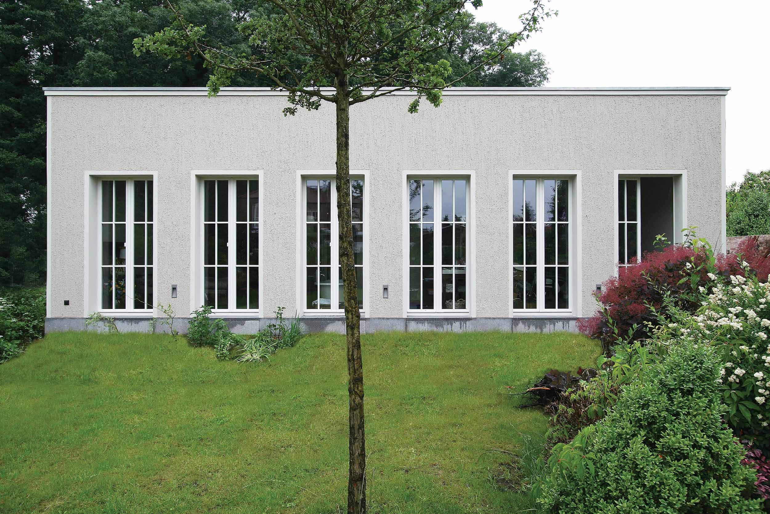 Die Gartenfassade mit klarer Fassadengliederung und bodentiefen französischen Fenstern