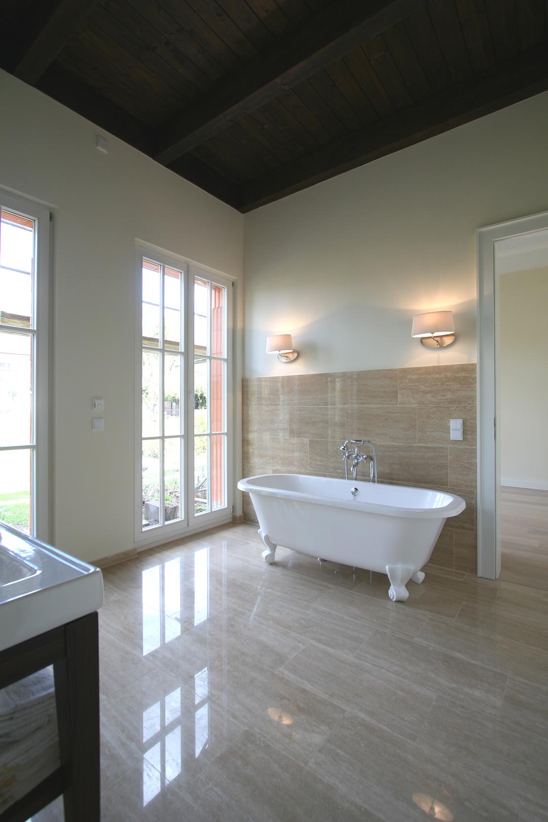 Das Masterbad mit freistehender Badewanne, dunkler Holzbalkendecke und Natursteinverkleidungen