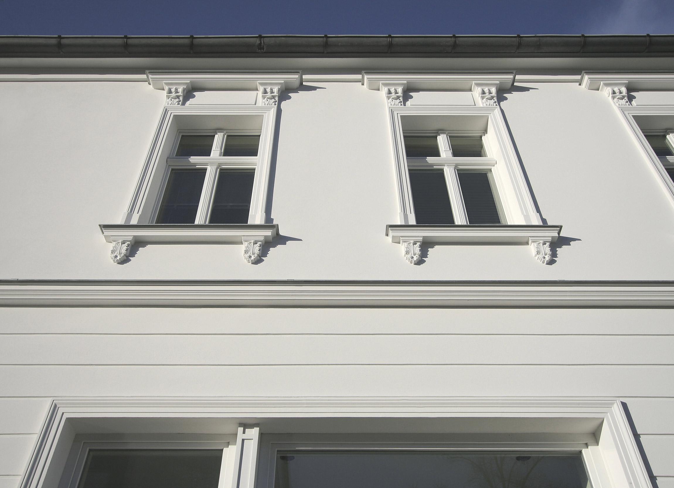 Fassadendetail mit Fensterverdachungen mit Stuckmörtel in Handarbeit hergestellt