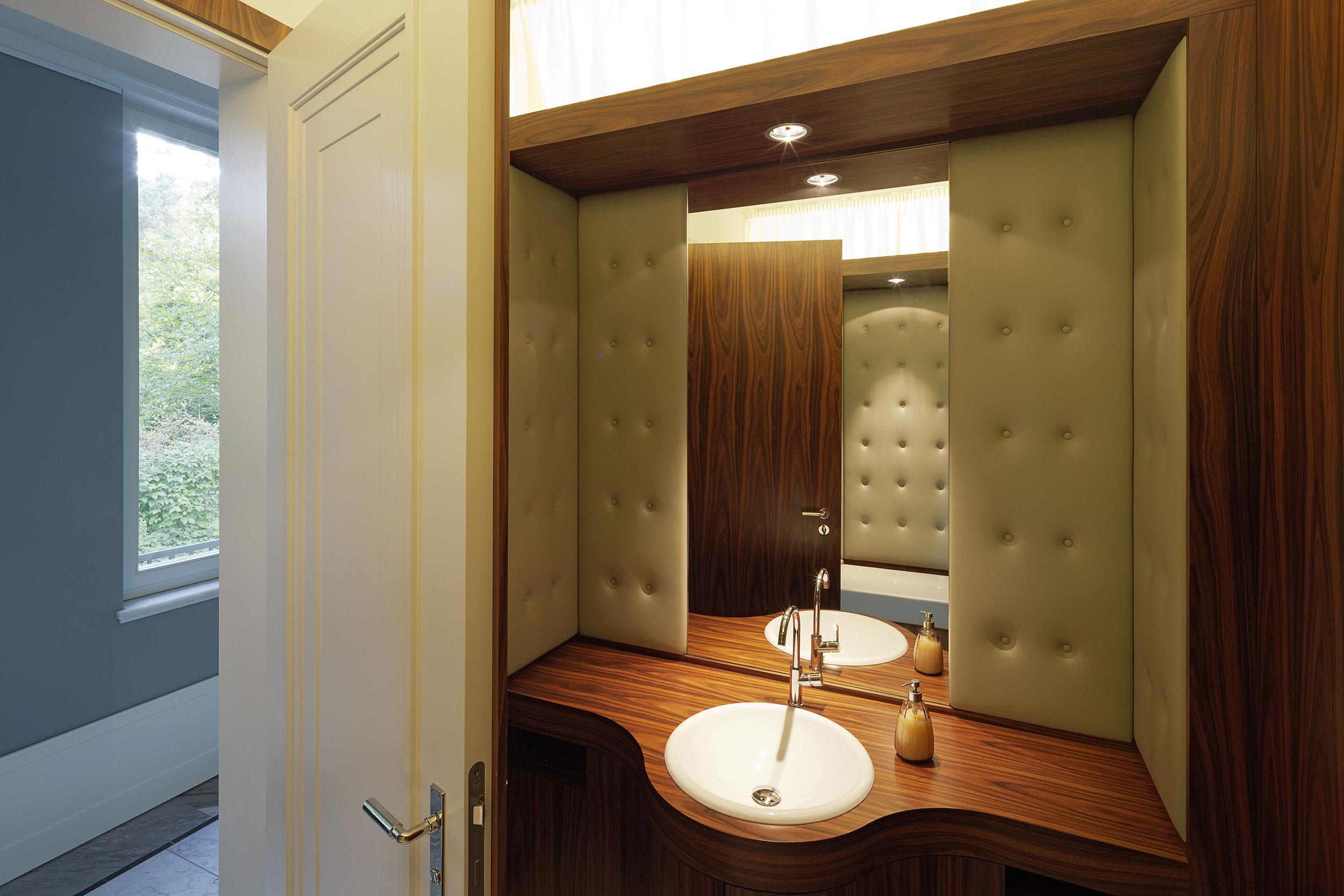 Neubau einer Villa im neoklassizistischen Stil - Das Gäste WC mit Lederpolsterungen und Wandvertäfelungen aus Palisanderholz