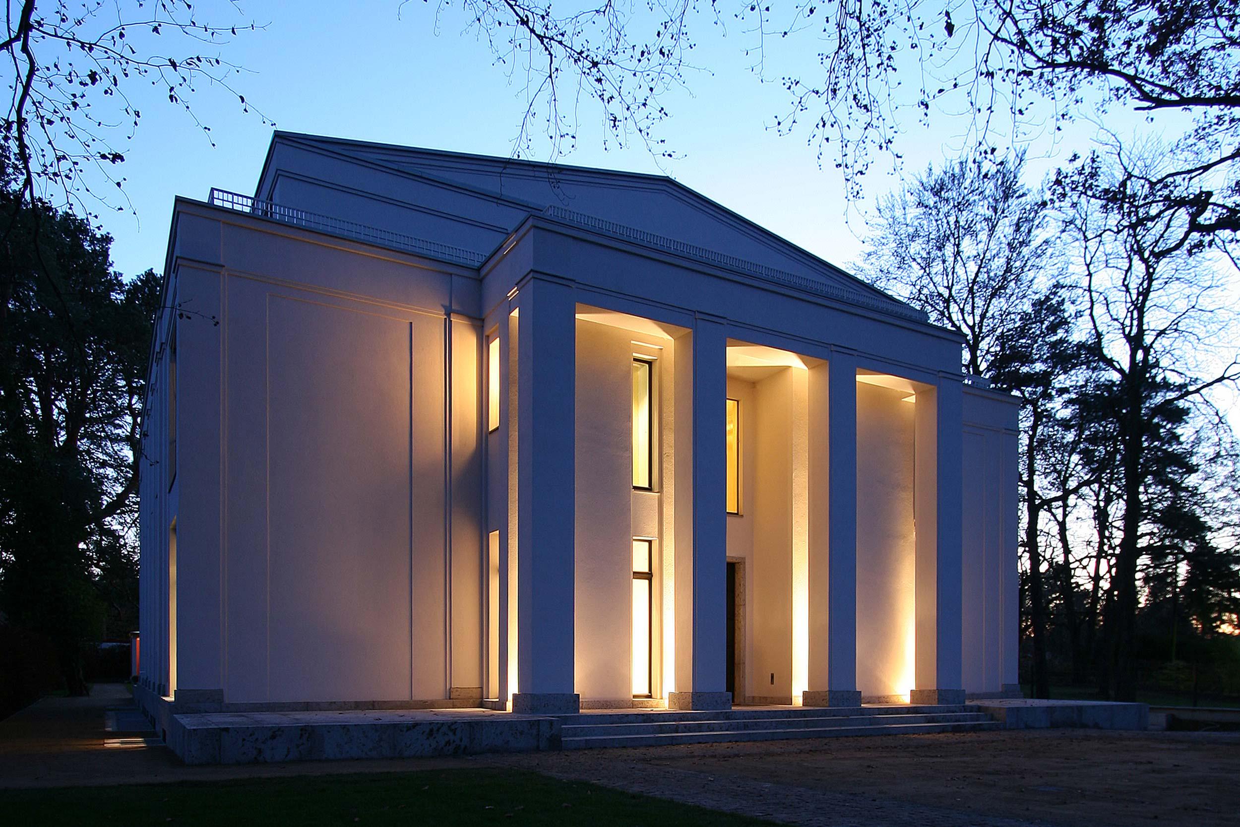 Neubau einer Villa im neoklassizistischen Stil - Das Hauptportal mit massiven Säulen und Giebeldreieck bei abendlicher Dämmerung