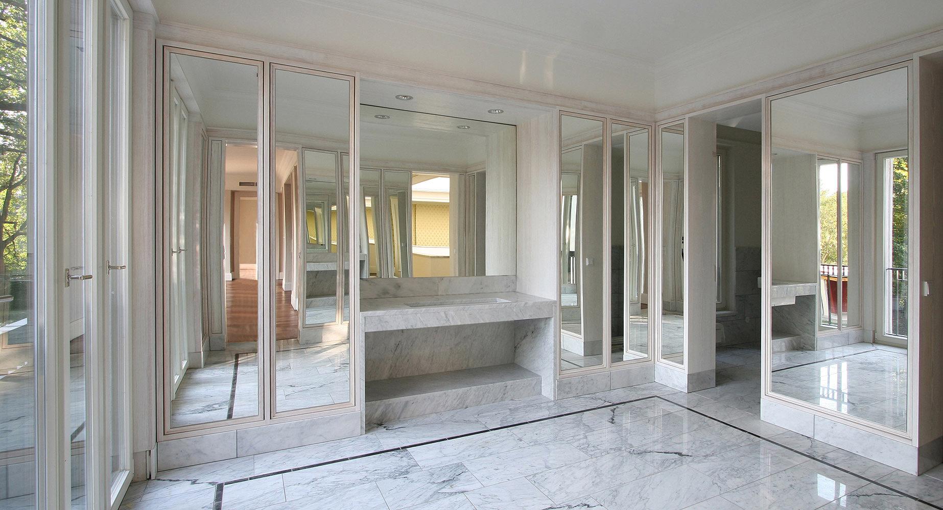 Neubau einer Villa im neoklassizistischen Stil - Das Masterbad mit Marmorboden und Schrankbereichen als umlaufende Spiegelwände