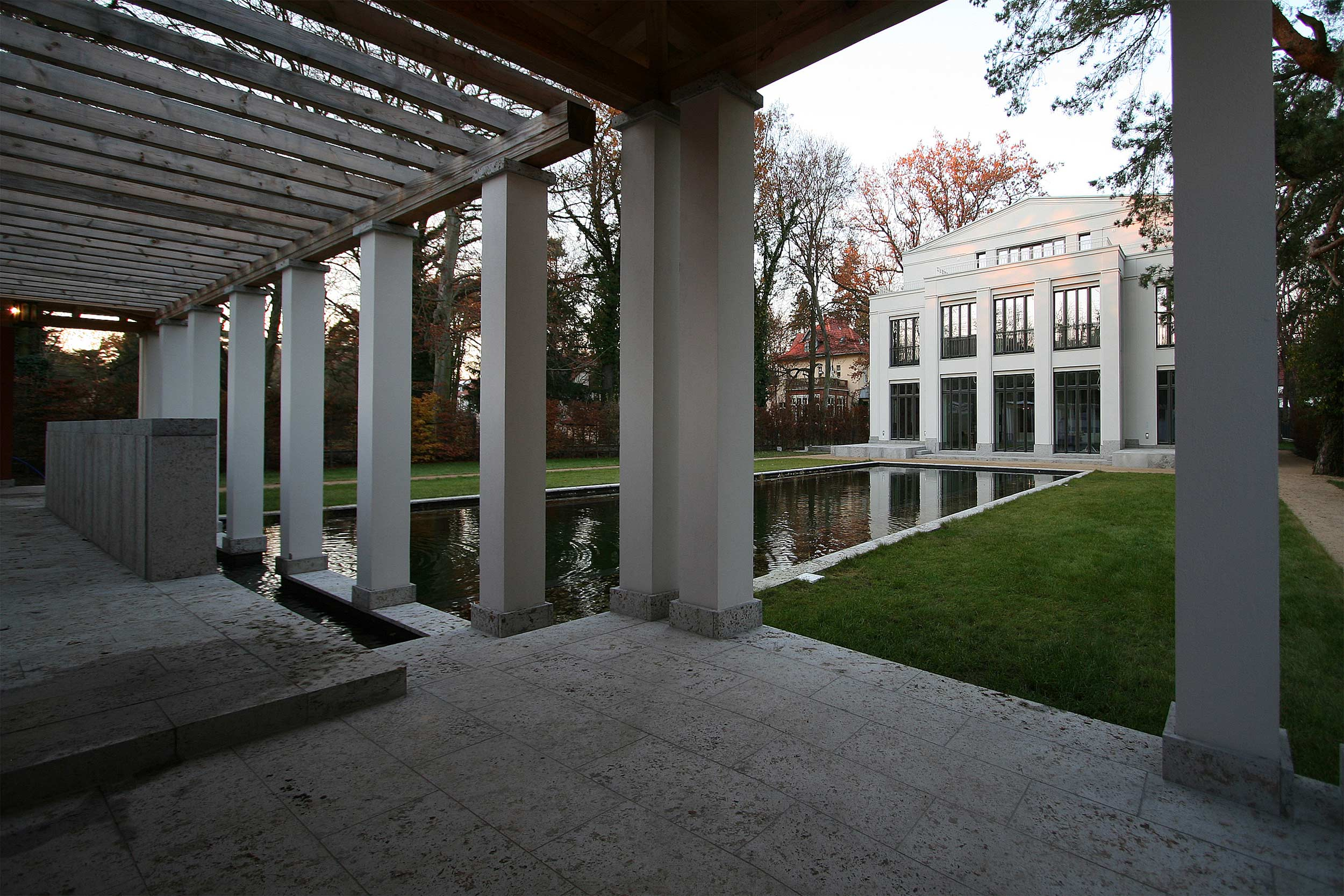 Neubau einer Villa im neoklassizistischen Stil - Schwimmteich, Pergolen und Pavillione haben einen Bodenbelag aus Muschelkalk