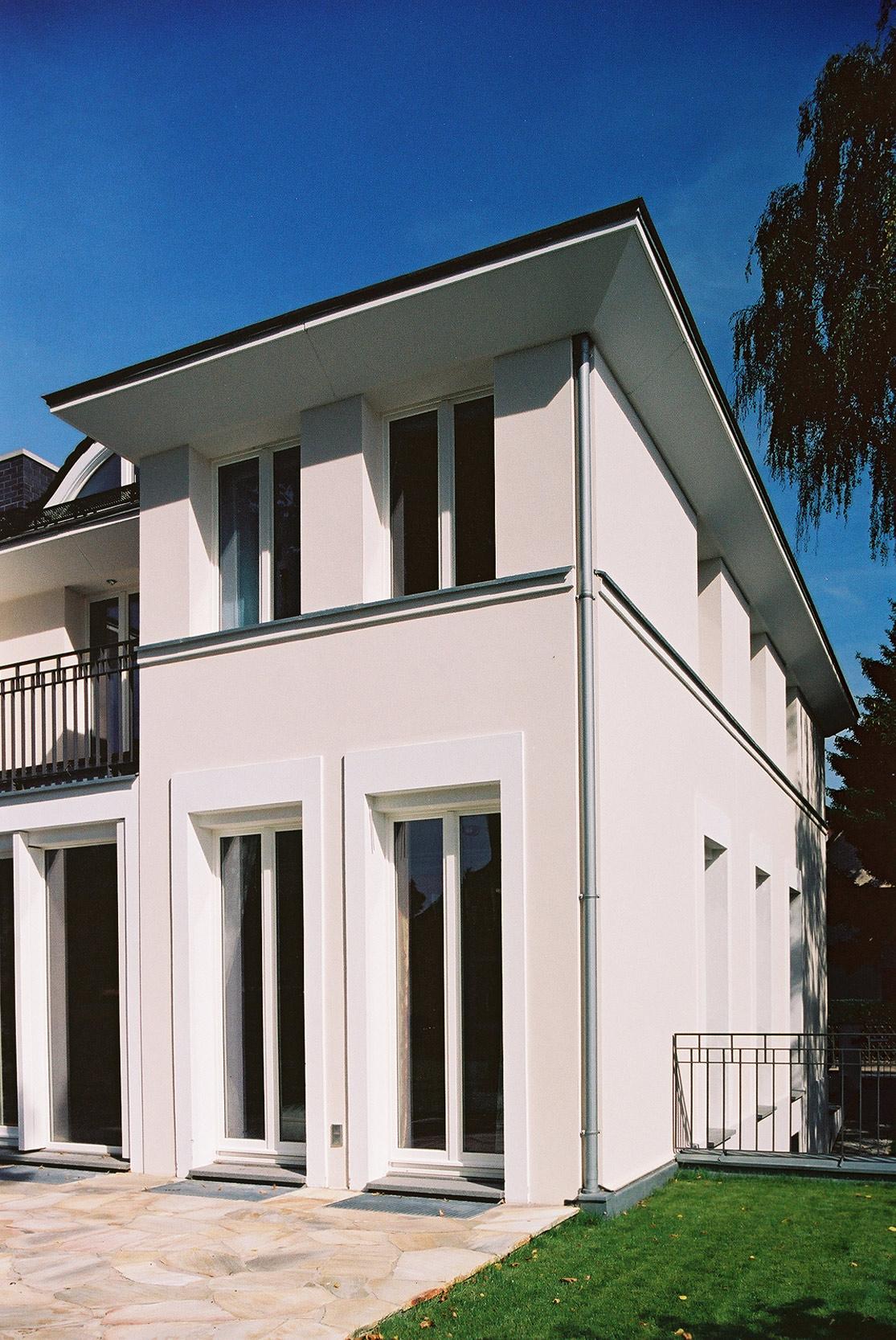 Französische Fenster und eine weit auskragende Attika vergfeinnern die Fassade des Hauses.