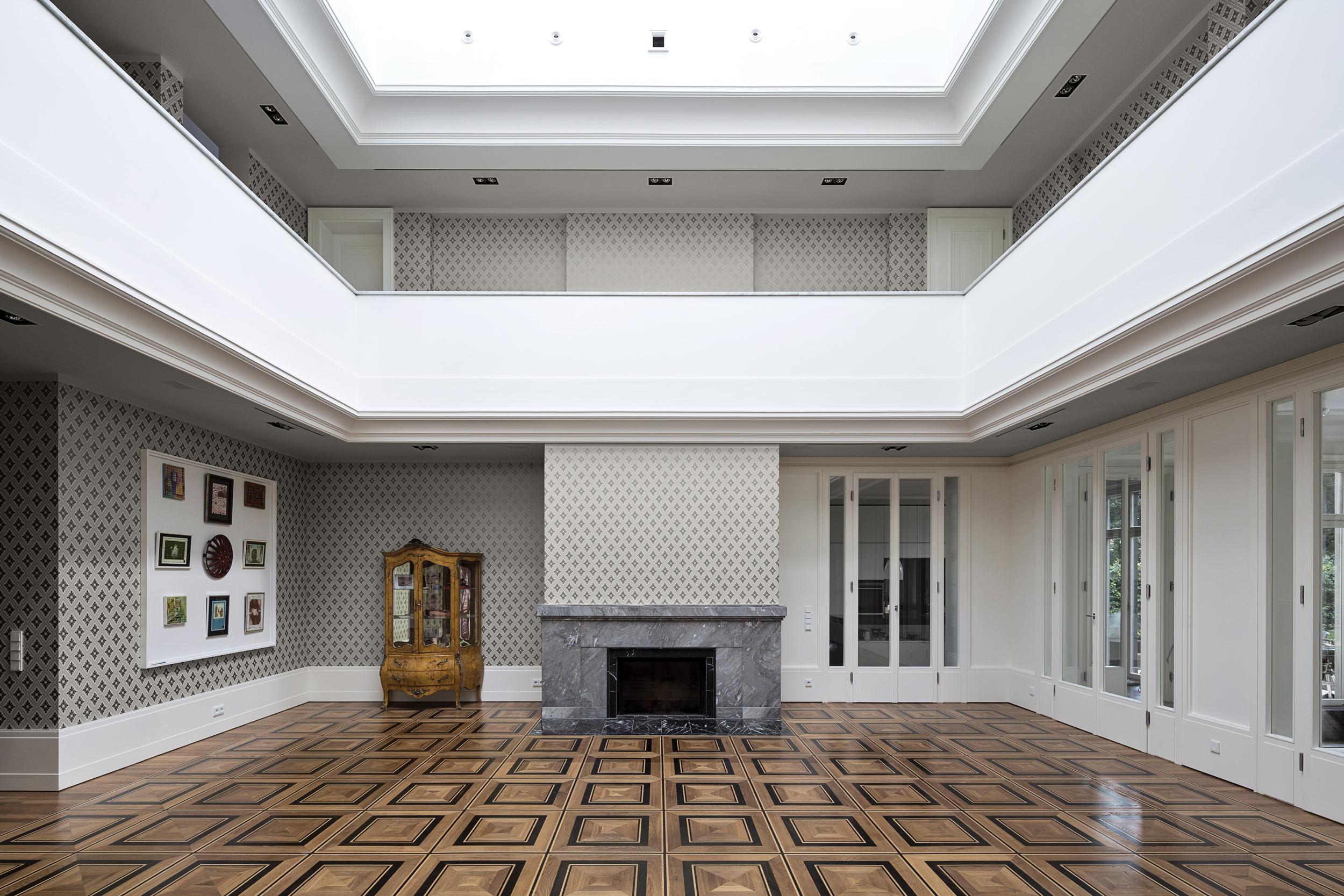 Neubau einer Villa im neoklassizistischen Stil - Die Halle mit Galerieebene handgerfertigtem Tafelparkett und profiliertem Marmorkamin