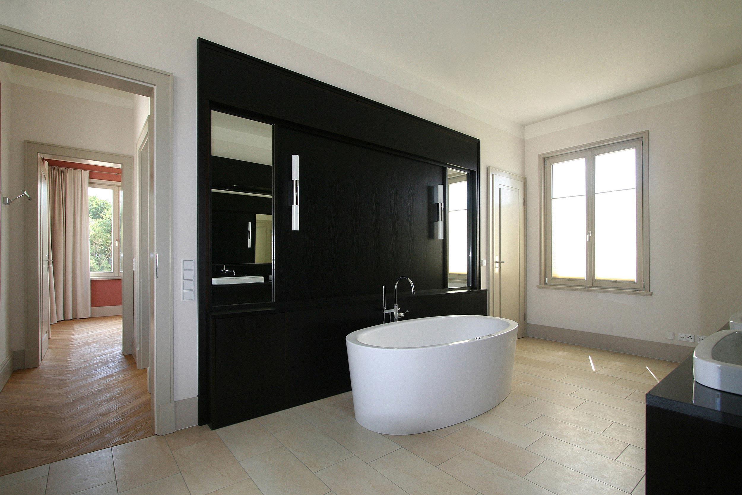 KLASSIK UND TRADITION - Neubau klassizistische Villa - Das Masterbad mit frei stehendem Whirlpool und Wandverkleidung.