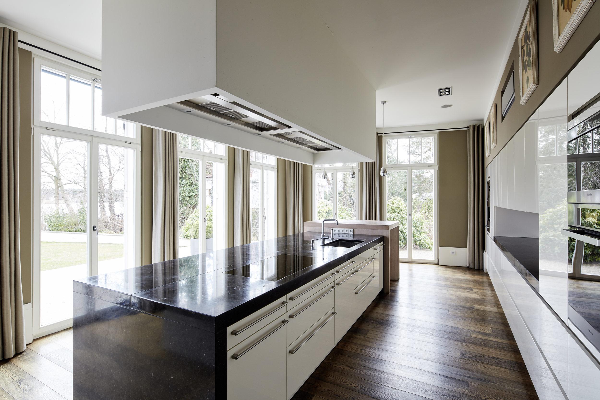Neubau einer Villa in klassisch-traditioneller Architektursprache am See - Die Küche mit Kochblock aus Blaustein und Abzugshaube aus Sonderfertigung