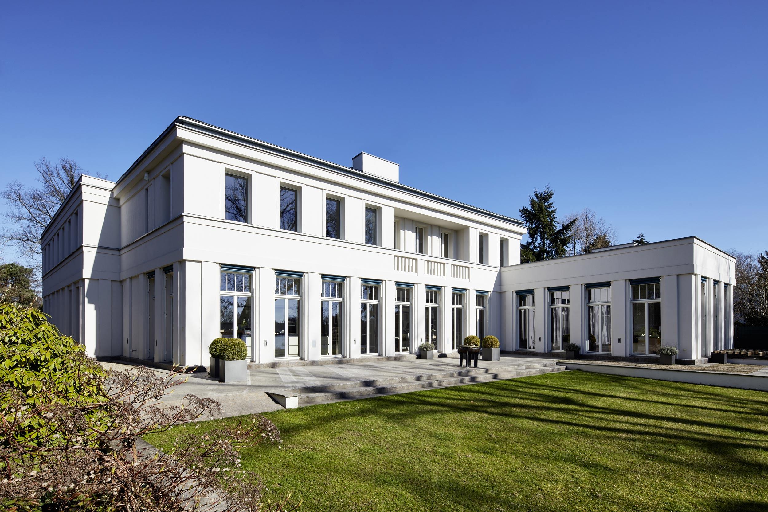 Neubau einer Villa in klassisch-traditioneller Architektursprache am See - Zur Seeterrasse im Süden hin sind Küche, Wohn- und Essbereich vollverglast.