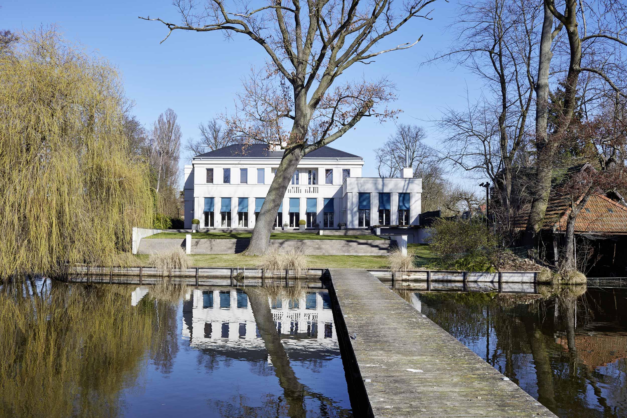 Neubau einer Villa in klassisch-traditioneller Architektursprache am See - Die Seelage der Villa mit Blick von der Steganlage auf das Seeufer
