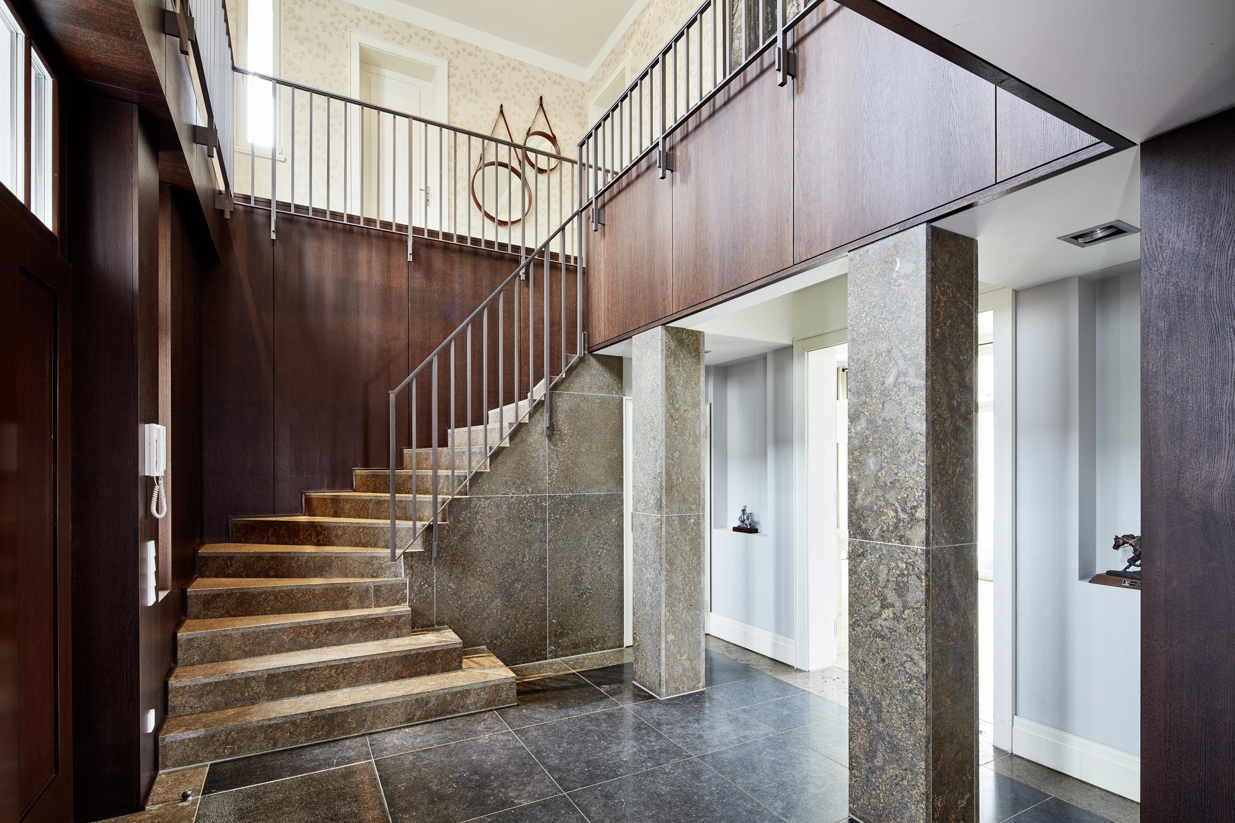 Neubau einer Villa in klassisch-traditioneller Architektursprache am See - In der Treppenhalle dominieren Naturstein und Wandvertäfelungen aus Eiche.