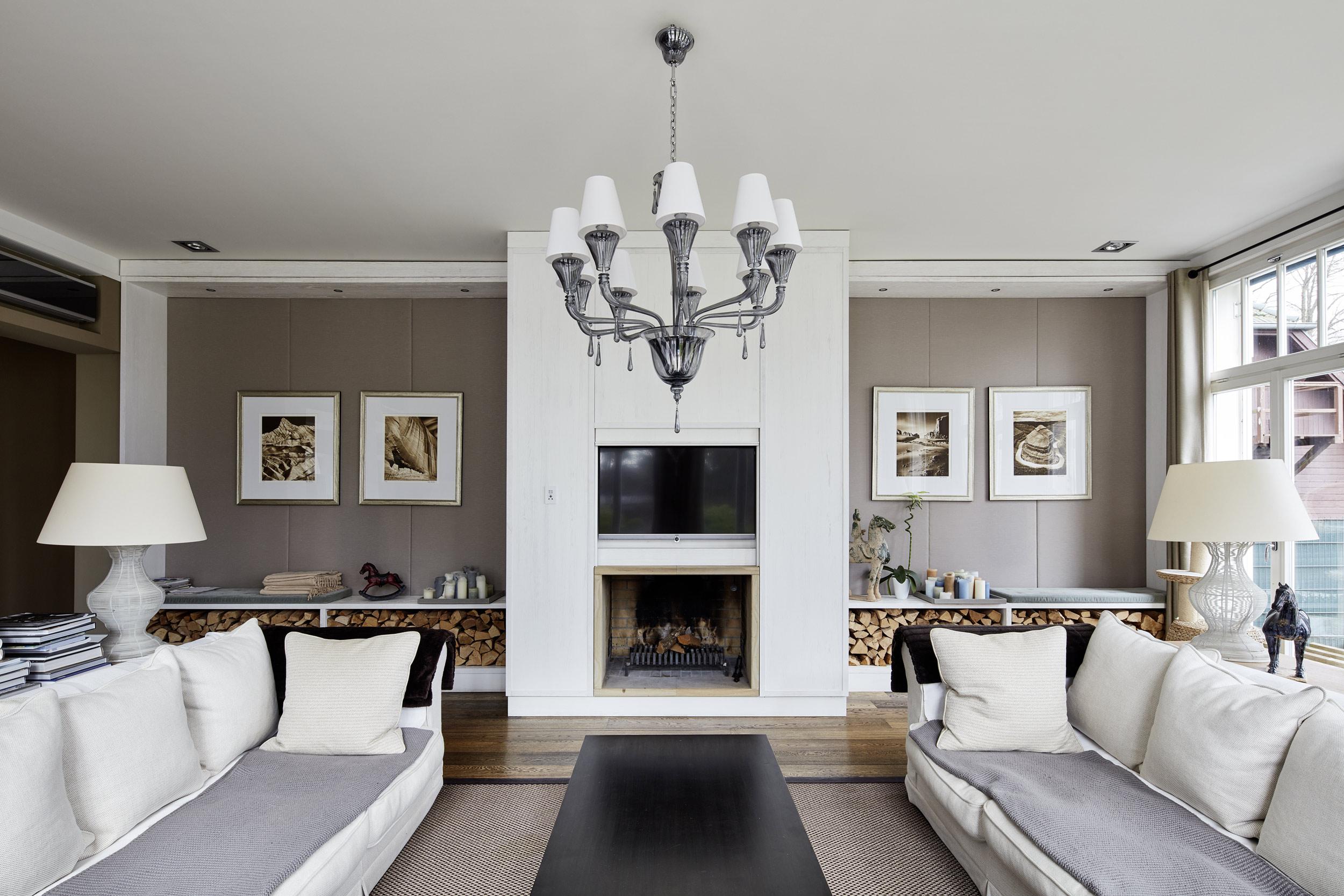 Neubau einer Villa in klassisch-traditioneller Architektursprache am See - Der Wohnbereich mit Vertäfelungen von Kamin und Wänden aus Holz und Stoff.