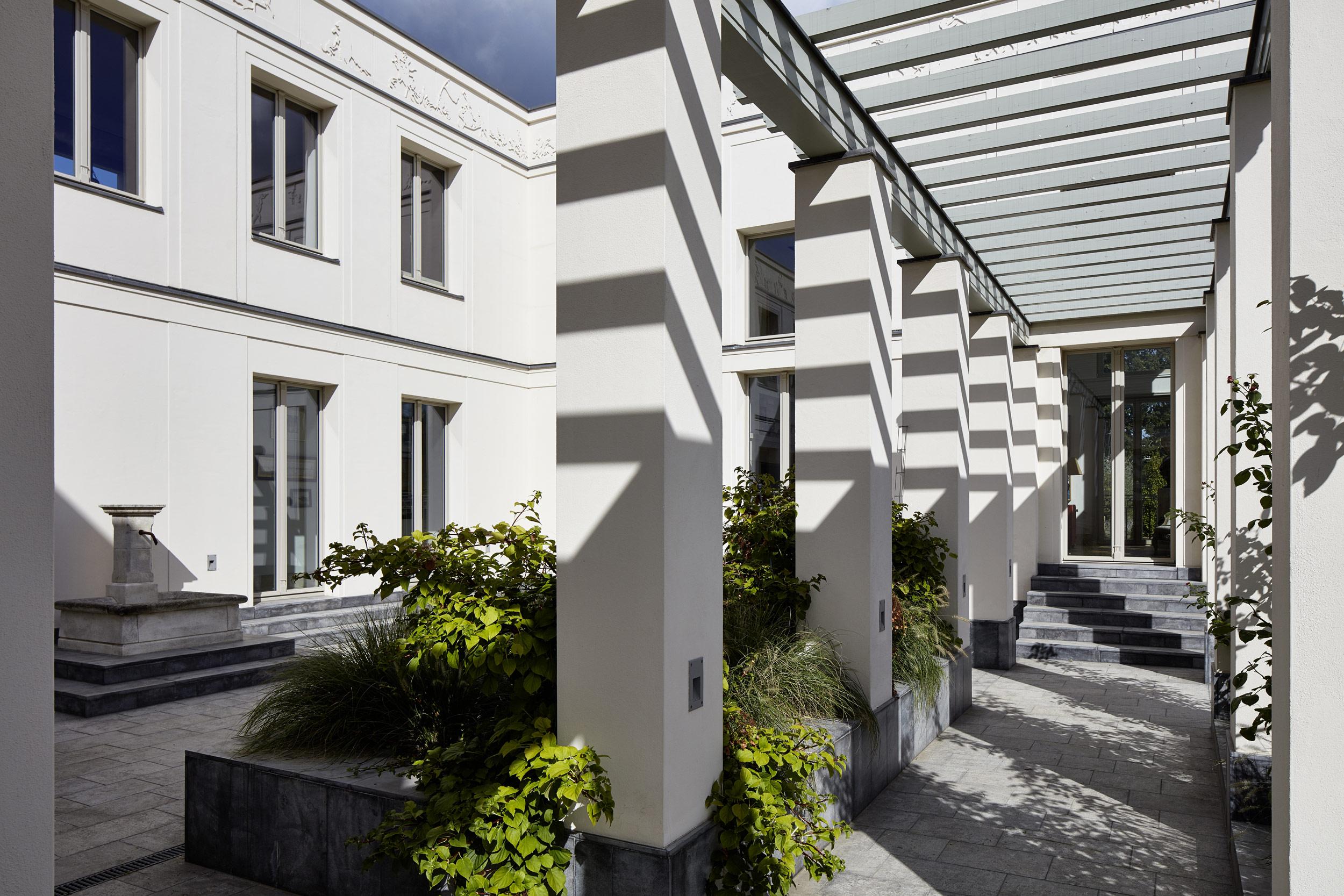 Klassik und Tradition - Eine berankte Pergola ermöglicht den Bewohnern der Villa eine Verbindung beider Seitenflügel über den Patio.