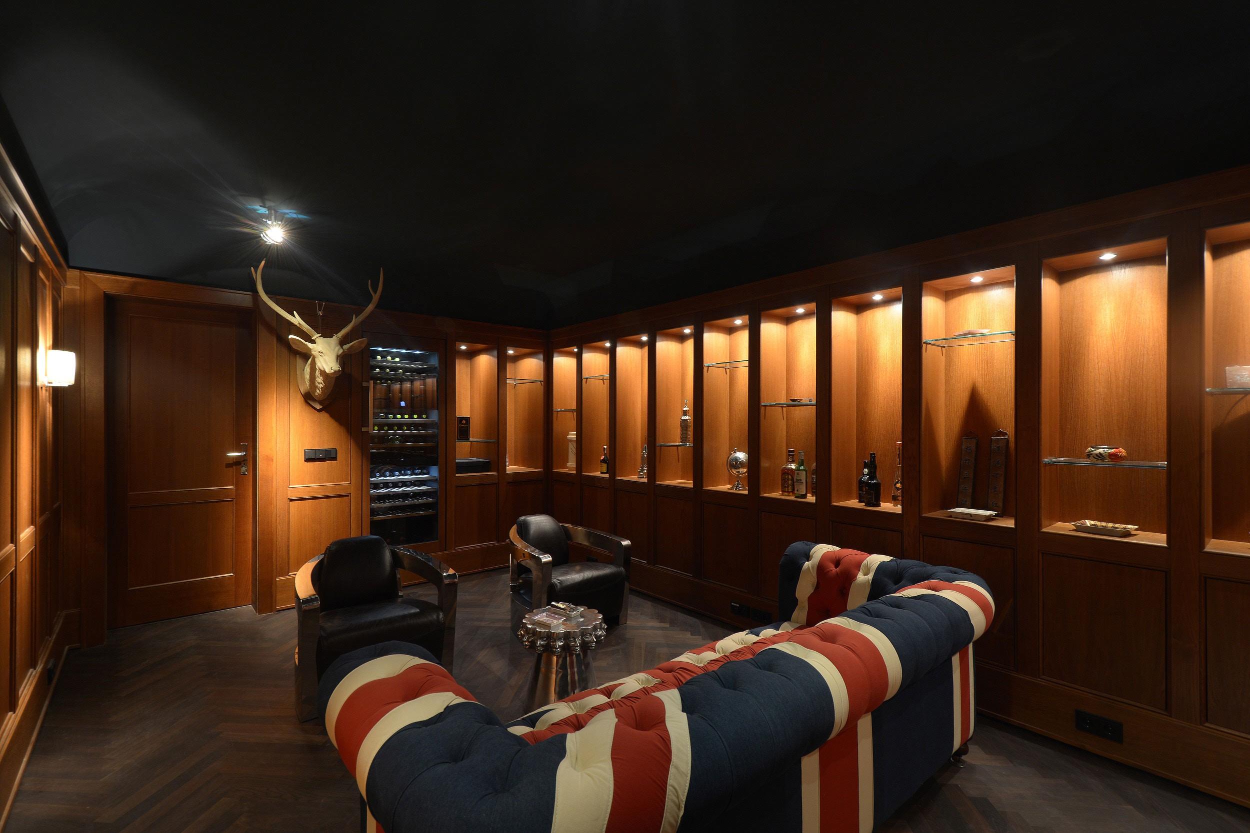 Neubau klassizistische Villa - In der Raucherlounge im Souterrain werden im Ambiente eines Members-Clubs in dunkler Wandvertäfelung Zigarren geraucht.
