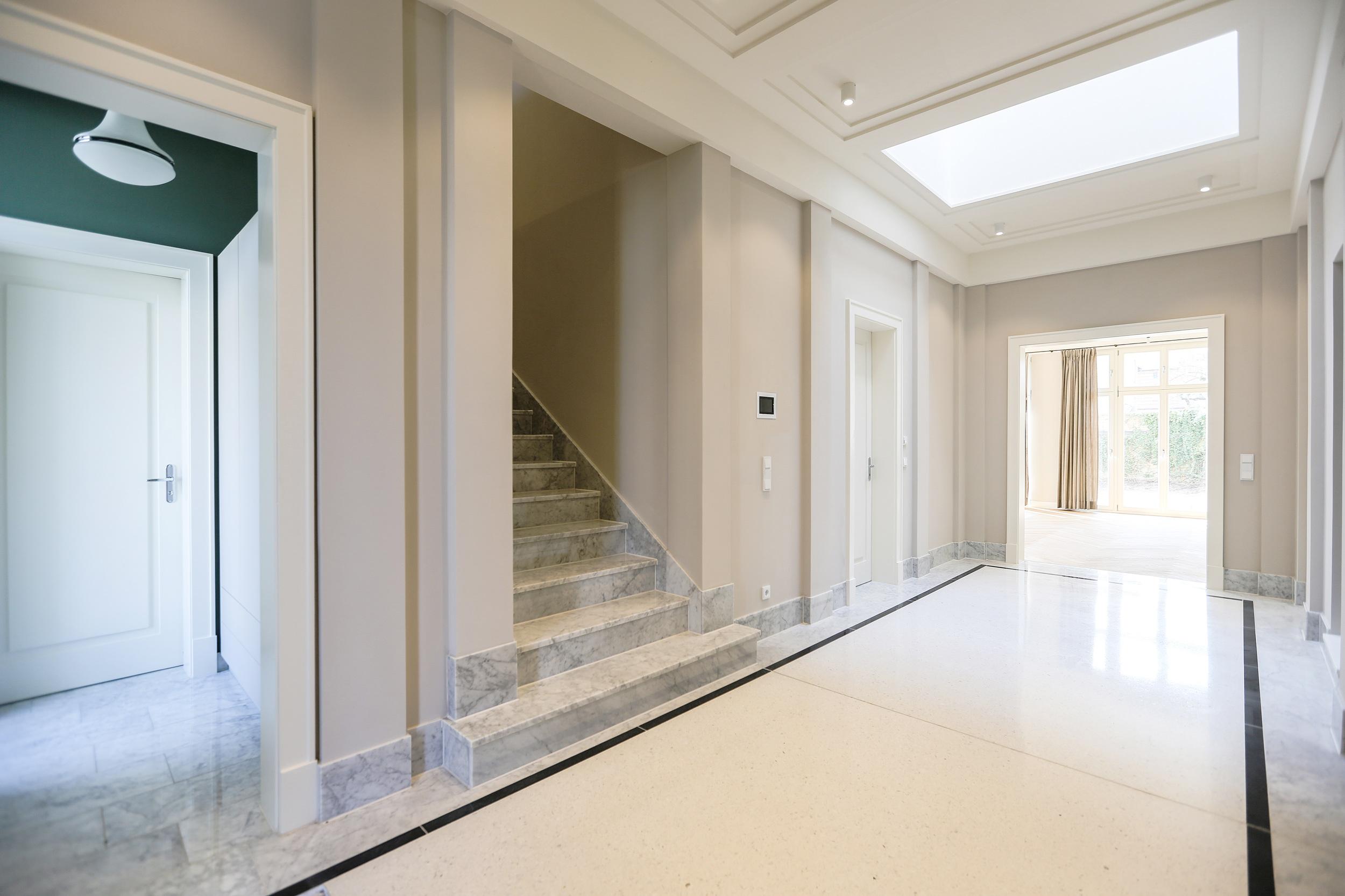 Neubau einer Villa im Klassik-Stil in Potsdam - Die großzügige Eingangshalle wurde mit italienischem Terrazzo und profilierten Deckenkassetten gestaltet.