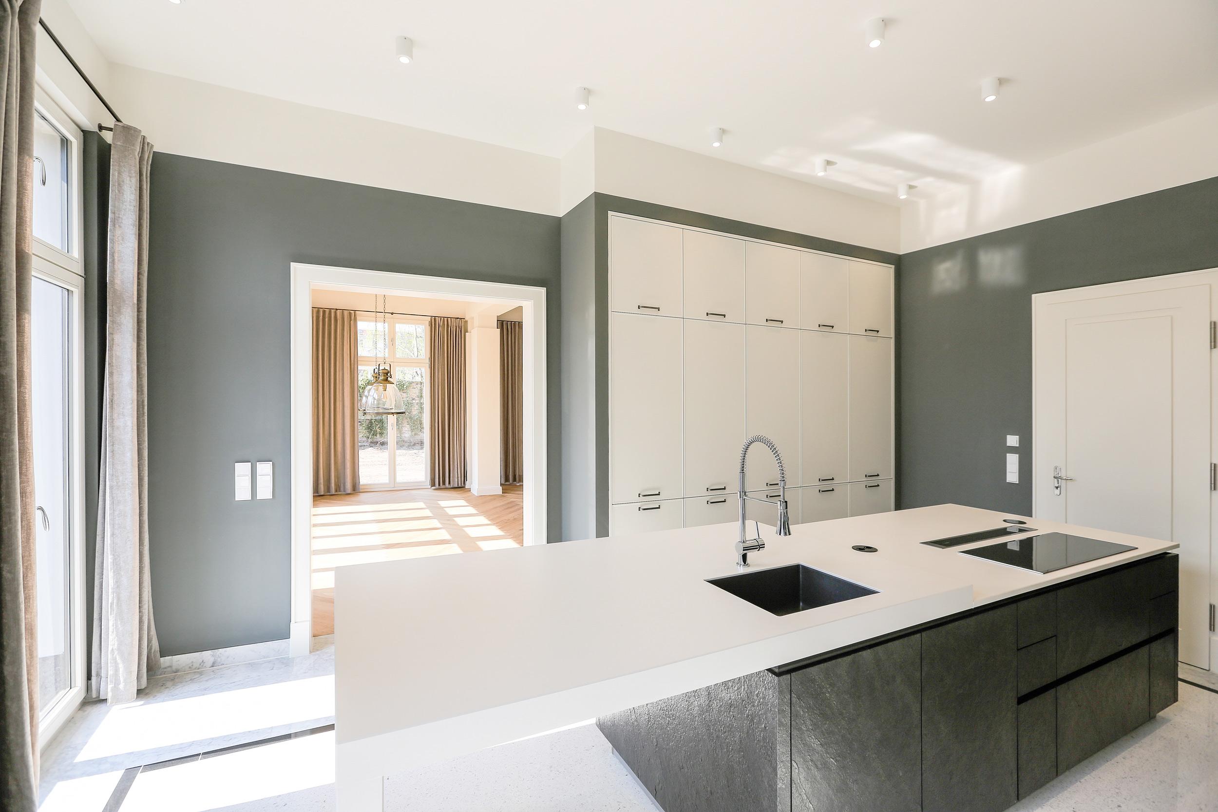Neubau einer Villa im Klassik-Stil in Potsdam - Die Küche und das Esszimmer haben eine offene Verbindung über Doppeltüren.