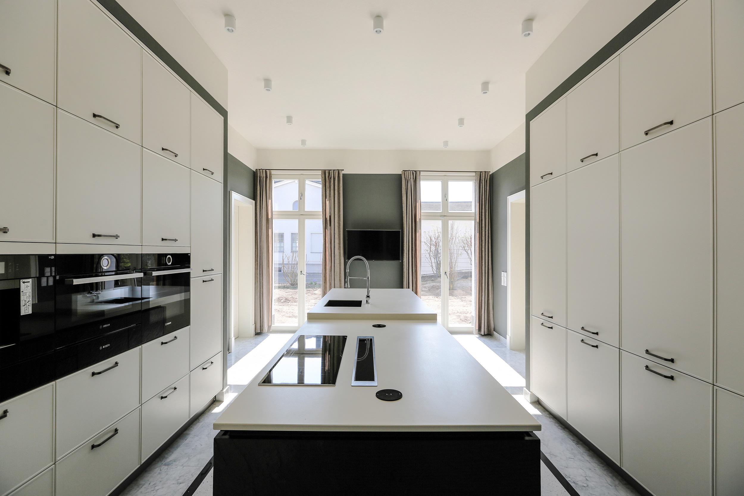 Neubau einer Villa im Klassik-Stil in Potsdam - Der Küchentresen wurde als Mittelblock zentral in der Küche angeordnet.