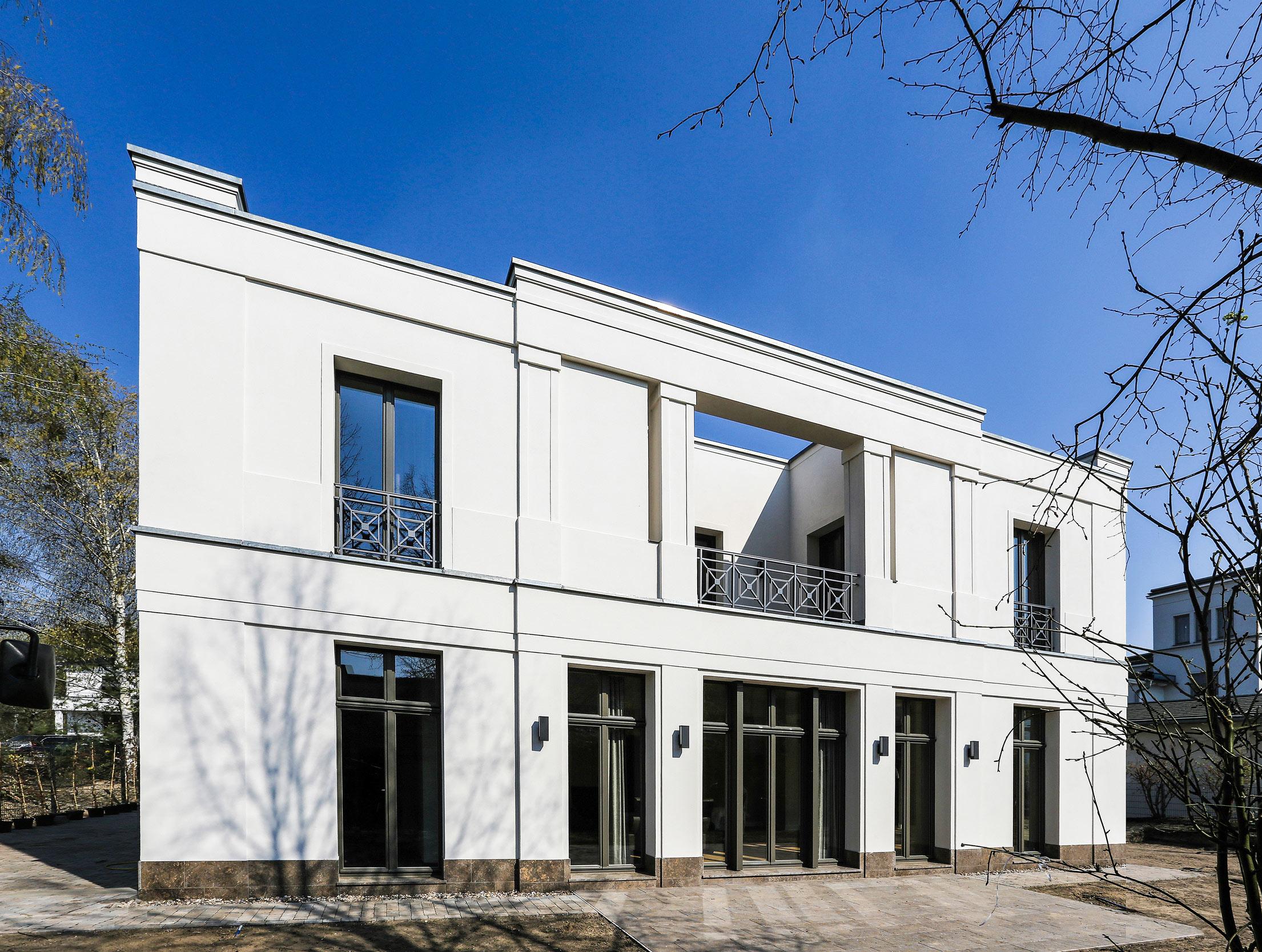 Neubau einer Villa im Klassik-Stil in Potsdam - Die Gartenseite mit Pergola und Loggia im Obergeschoss und der Gartenterrasse.