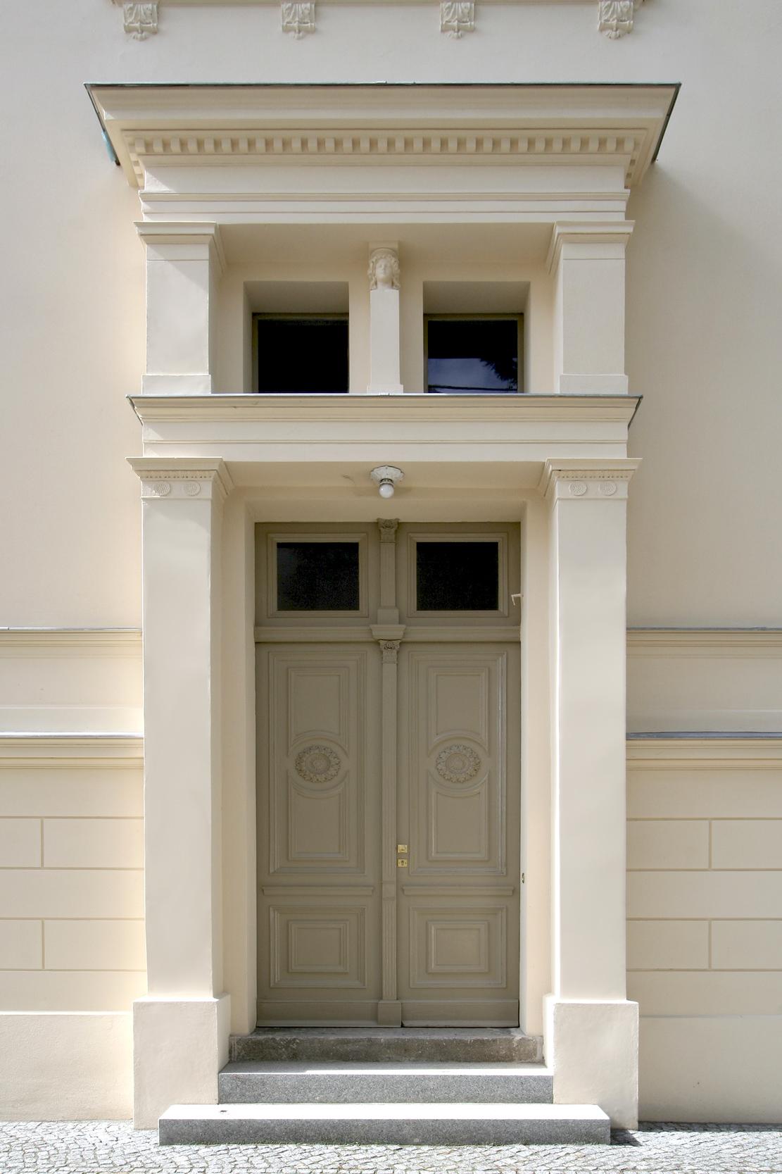 Das Eingangsportal prägt in in klassizistischer Zurückhaltung die Doppelflügeltür mit darüber liegenden Oberlichtern.