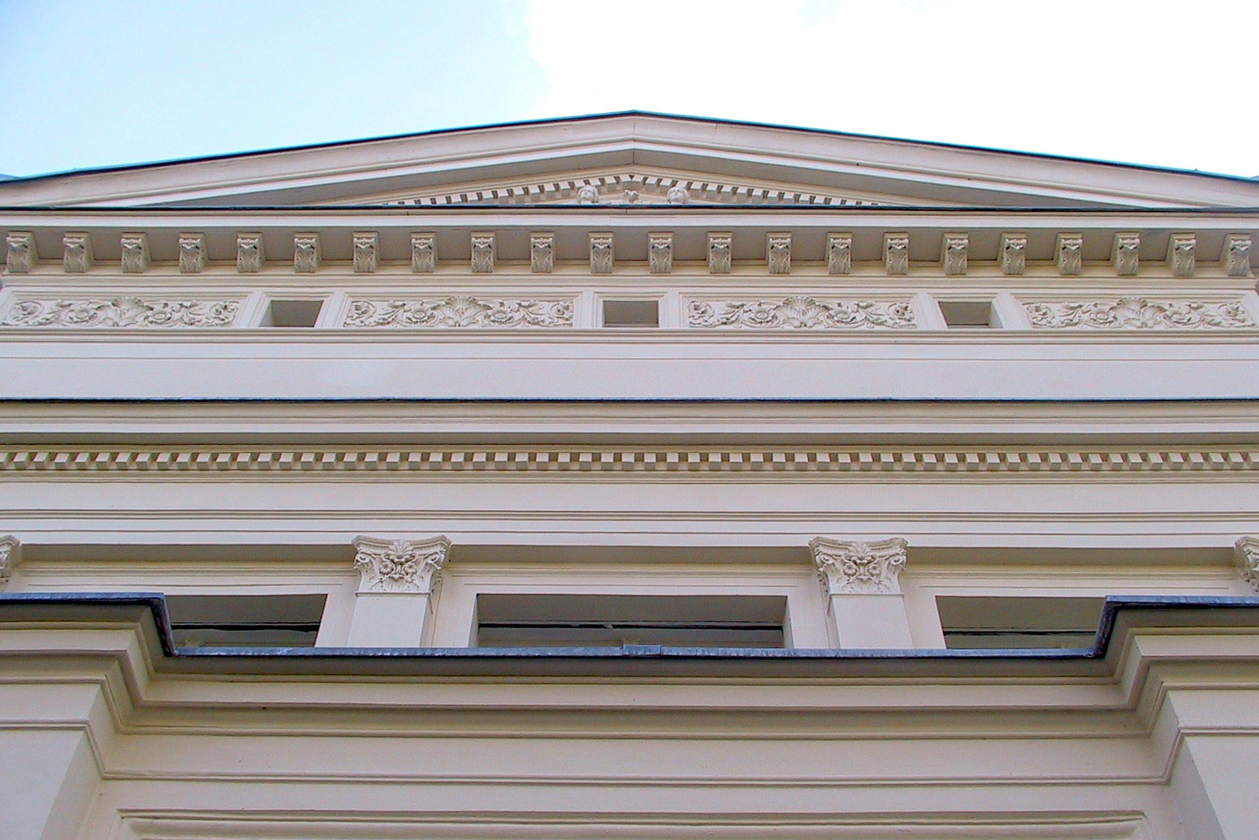 Das Giebeldreieck der Hauptfassade in klassizistischer Tradition mit Zahnfriesreihen und Gesimsbändern.